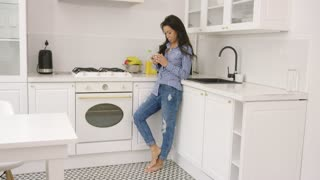 Side view of casual young woman using smartphone while leaning on counter in modern light kitchen.