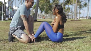 Side view of cheerful handsome man holding legs of charming black girl while working out on abs in green sunny park.