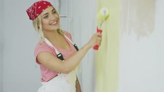 Side view of cheerful young gorgeous woman in red bandana and white overalls painting plastered wall with roller in pastel yellow color
