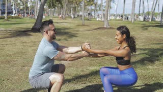 Side view of diverse man and woman in sportswear helping each other and doing squat holding hands in sunlight.
