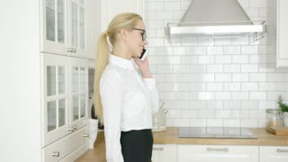 Side view of laughing attractive woman wearing formal clothing and talking by phone while standing at kitchen.