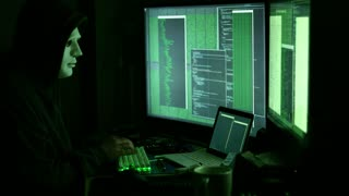 Side view of man in mask and hood hacking worldwide network using modern computers and gadgets.