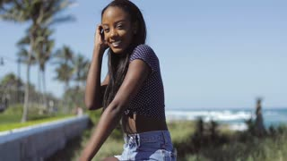 Side view of pleased young ethnic woman standing at the fence on street and looking at camera while smiling at seaside.
