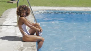 Side view of pretty attractive black woman sitting on pool edge and relaxing in sunny day.