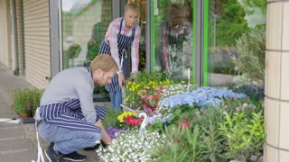 Side view of two young people in uniform working and taking care of flowerbed outside of flower shop in summer day.