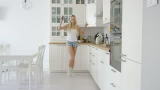 Side view of young beautiful woman holding phone in hand and dancing at home in light kitchen.