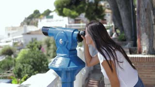 Side view of young brunette in casual clothing posing on viewpoint and exploring tropical city in sunlight using spyglass.