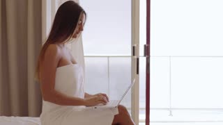 Side view of young charming woman wrapped in white towel and posing on hotel bed using laptop with background of ocean.