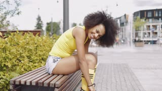 Side view of young ethnic girl in trendy sportive clothing putting on rollerblades while sitting on wooden bench on background of street.
