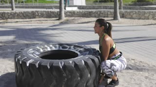 Side view of young fit woman in sportswear sitting at huge tire and trying to lift it while working out in the park.