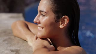 Side view of young happy woman daydreaming and looking away with smile while refreshing in hotel pool.