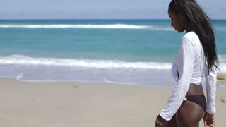 Side view of young pretty black woman in white shirt standing on background of blue ocean and looking at camera.