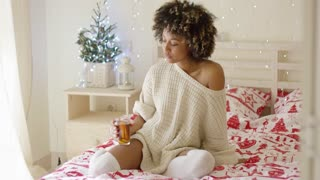 Single beautiful young adult african american woman wearing white knitted sweater sipping tea while seated in bed. She has beautifully decorated bedroom for Christmas time.