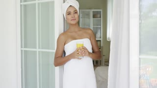 Single beautiful young woman holding glass of orange juice while wrapped in towel and leaning on outside door