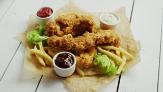 Small bowls with assorted sauces and pile of palatable fried chicken wings lying on parchment paper on white wooden tabletop