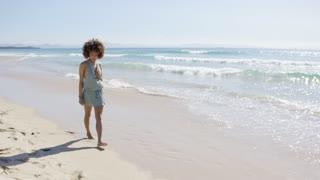 Smiling beautiful female wearing jumpsuit walking along beach looking at camera. Tarifa beach. Provincia Cadiz. Spain.