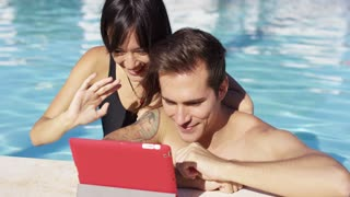 Smiling couple in swimming pool use digital device on a lovely summer afternoon