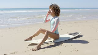 Smiling female sitting on surfboard and looking at camera in Tarifa beach in sunny day. Cadiz, Spain.