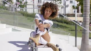 Smiling female sitting on white stairs wearing roller skates, knee-high socks and t-shirt looking at camera.
