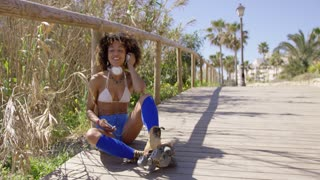 Smiling female wearin swimsuit top, blue shorts and roller skates sitting listening music with headphones.