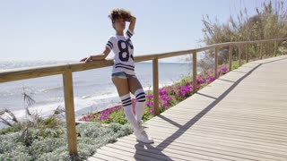 Smiling female wearing sportive knee-high socks and t-shirt leaning on fencing of sidewalk on background of ocean.