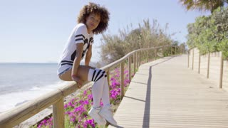 Smiling female wearing sportive knee-high socks and t-shirt sitting on fencing of sidewalk on background of ocean.