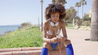 Smiling female wearing swimsuit top and shorts sitting on curb with headphones on her neck using smartphone.
