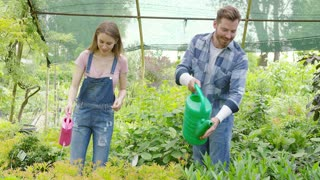 Smiling girl in overall and happy man watering fresh green plant with pots standing inside of greenhouse of garden.