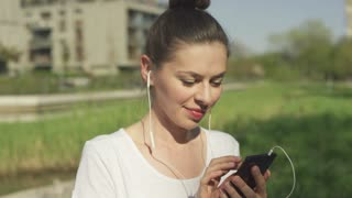 Smiling glorious woman wearing headphones using smartphone and squinting against sunlight