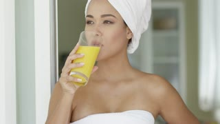 Smiling healthy young woman with a white towel around her hair drinking fresh orange juice close up head and shoulders