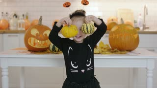 Smiling little girl in cute Halloween costume standing in front white table with jack-o-lanterns and holding two small pumpkins.