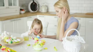 Smiling young woman helping little girl to color Easter eggs while sitting by table at light kitchen.