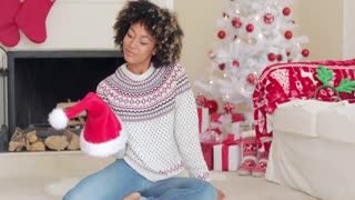 Smiling young woman holding a Santa hat as she relaxes on the floor in a red and white themed Christmas living room at home
