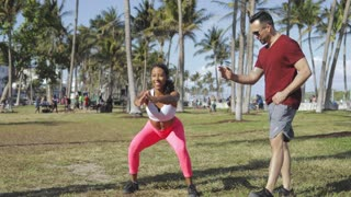 Sportive fit black woman doing dynamic lunges with help of personal instructor in green tropical park on green lawn.