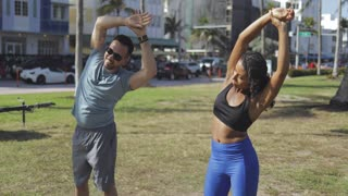 Sportive man showing exercise to young black woman in sportswear helping with healthcare training in tropical park.
