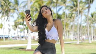 Stylish playful ethnic model in summer outfit pouting lips and posing at camera of phone taking selfie in summertime.