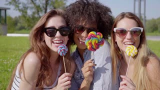 Three young black and white women eating lollipops and looking at camera in the park.