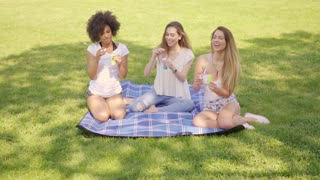 Three young black and white women sitting on lawn in park and blowing soap bubbles together.