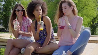 Three young multiethnic women sitting in park and having refreshing drinks together.