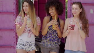 Three young multiracial women having fun and drinking refreshing beverages in the street.