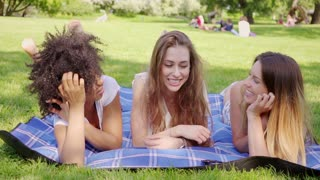 Three young pretty black and white girls talking and smiling lying on plaid in the park.