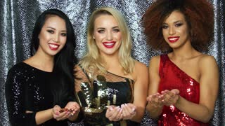 Three young pretty female models in glamour dresses standing together and blowing on glittering confetti on hands.