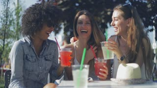 Three young women in summer clothing sitting at table with drinks in outside cafe and laughing while having fun