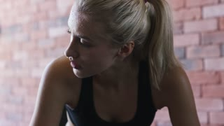 Tired young female with sweaty face looking away while sitting on background of brick wall and relaxing during training in gym