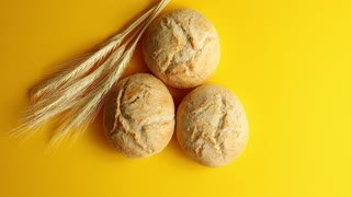 Top view of arranged round buns of crispy golden bread on yellow background with ears of wheat