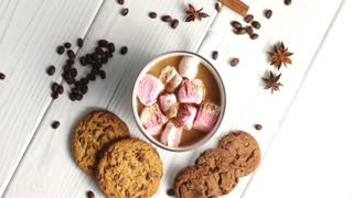 Top view of arranged white mug filled with cacao and sweet pink marshmallows on table with cookies and aromatic spices