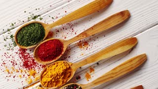 Top view of arranged wooden spoons filled with colorful assortment of spices on white wooden table