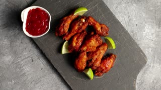 Top view of board with served fried chicken wings on it with slices of lime and bowl of tomato sauce