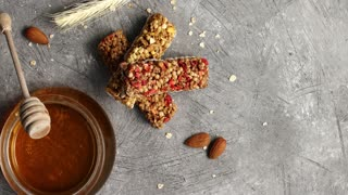Top view of composed cereal bars on gray surface with nuts and glass jar of golden honey