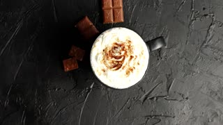 Top view of mug with cacao and white whipped cream powdered with cacao and served on table with milk chocolate